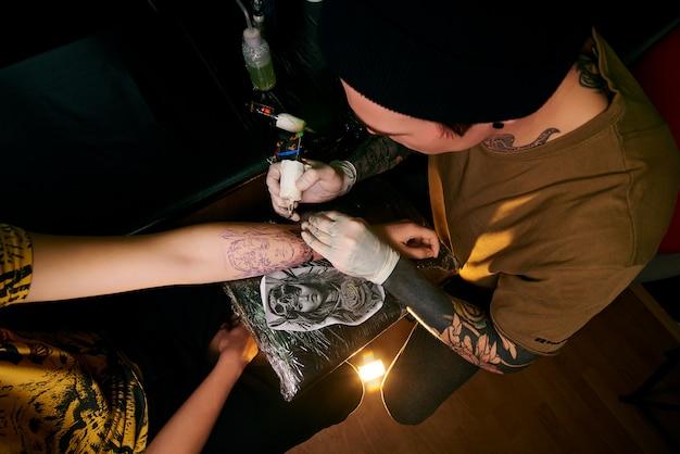 Knappe jonge kerel in een zwarte hoed en met tatoeages Premium Foto