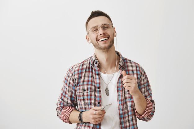 Knappe jonge kerel met een bril poseren met zijn telefoon en oortelefoons