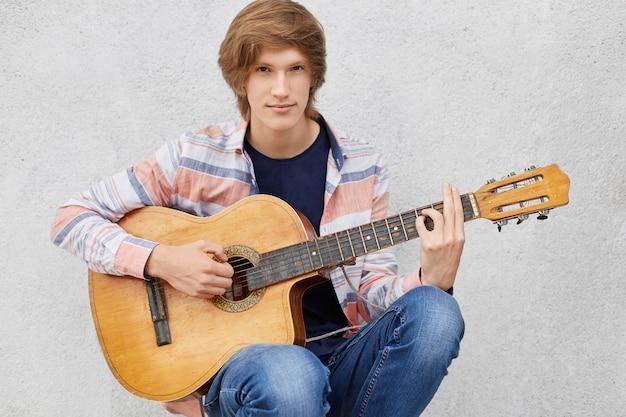 Knappe jonge kerel met stijlvolle kapsel dragen shirt en spijkerbroek gitaar spelen, liedjes zingen
