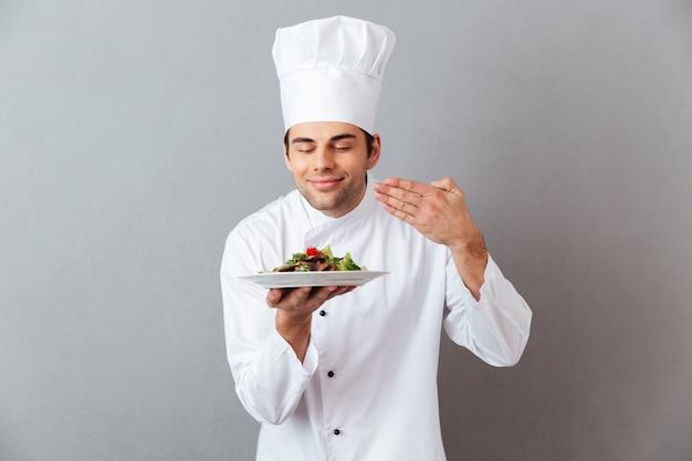 Knappe jonge kok in uniforme geursalade