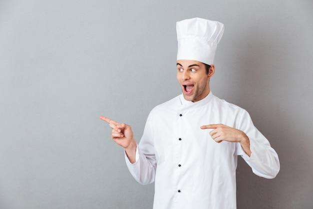 Knappe jonge kok in uniforme wijzen.