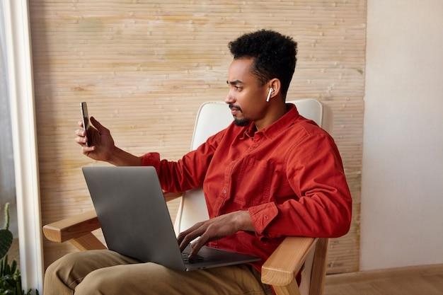 Knappe jonge kortharige bebaarde man met donkere huid hand opsteken met smartphone terwijl het nemen van portret van zichzelf op zijn mobiele telefoon, geïsoleerd op beige interieur