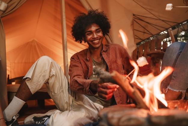 Knappe jonge, krullende afrikaanse man die marshmallows roostert op spiesjes boven de vuurplaats op de camping, genietend van een glampingvakantie in de buitenlucht met vrienden die weer samenkomen na een pandemische afsluiting.