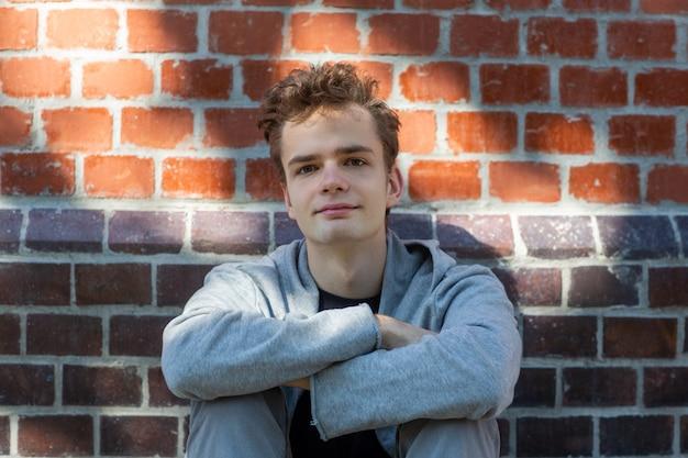 Knappe jonge lachende jongeman, tiener in een hoodie zit in de buurt van een bakstenen muur in de straat