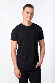 Knappe jonge lachende man draagt een zwart katoenen t-shirt met korte mouwen en zwarte jeans poseren.