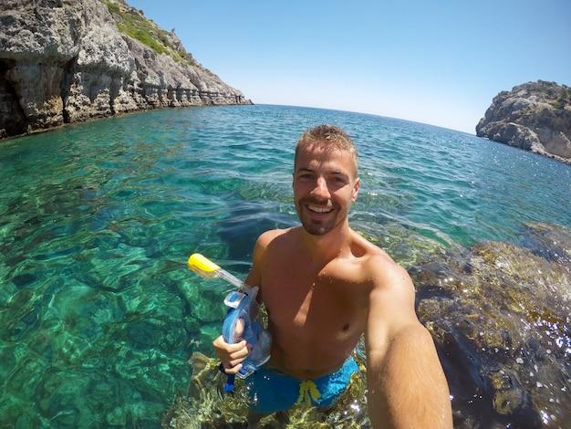Knappe jonge lachende toeristische man geniet van een zonnige dag en neemt een selfie met een mobiel terwijl hij op de steen in de zee staat en een snorkelmasker vasthoudt.