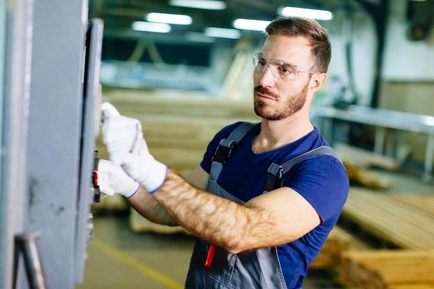 Knappe jonge man aan het werk in de meubelfabriek