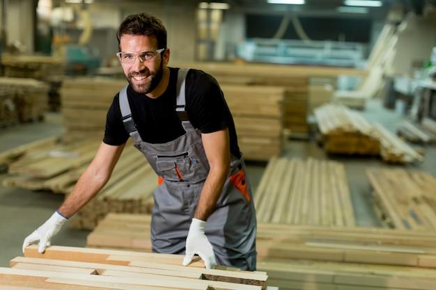 Knappe jonge man aan het werk in het hout fabriek