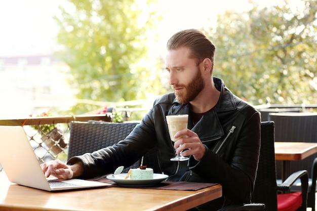 Knappe jonge man aan het werk op laptop in café