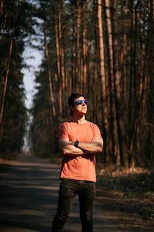 Knappe jonge man buiten in park, wandelen in het park