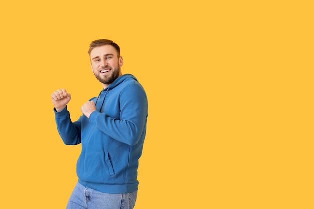 Knappe jonge man dansen tegen kleur achtergrond