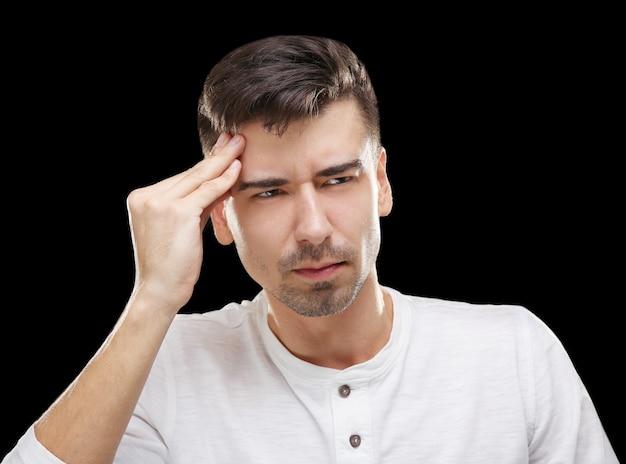 Knappe jonge man die aan hoofdpijn lijdt