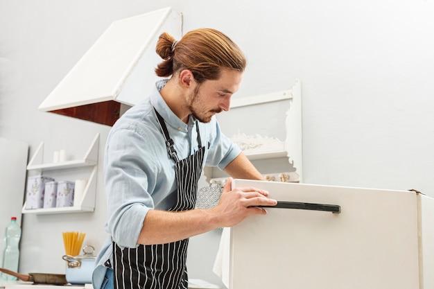 Knappe jonge man die een koelkast opent