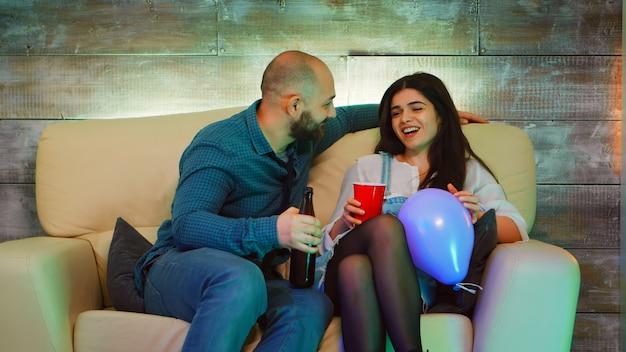Knappe jonge man die een mooi meisje aan het lachen maakt op het feest van zijn beste vriend. alcohol drinken.