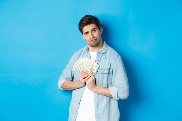Knappe jonge man die geld voor zichzelf houdt, glimlachend en hebzuchtig kijkt, staande over een blauwe achtergrond.