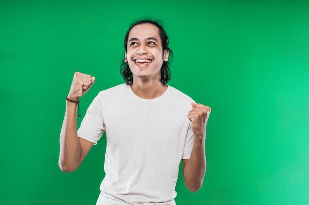 Knappe jonge man die geluk uitdrukt met gebalde vuisten en twee handen opgestoken