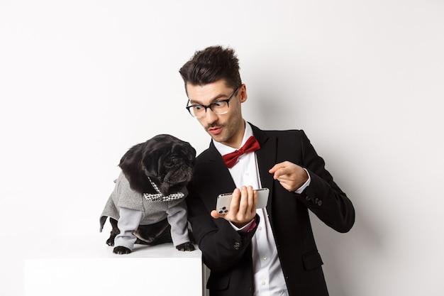 Knappe jonge man die iets op de mobiele telefoon laat zien aan zijn hond. eigenaar online winkelen met huisdier, staande in kostuums op witte achtergrond