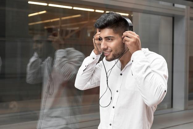 Knappe jonge man die lacht en muziek luistert op straat