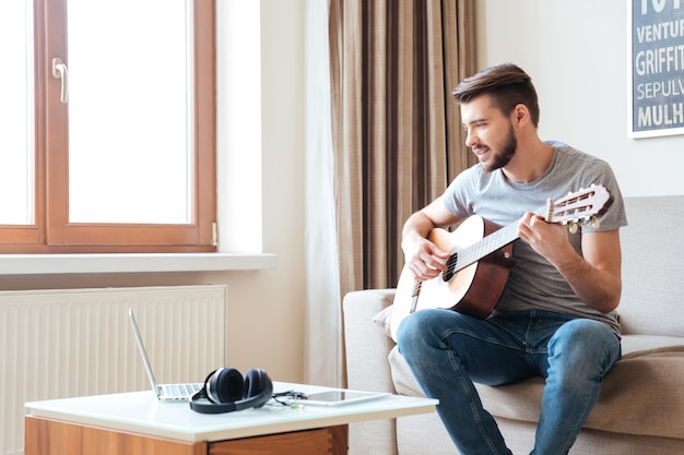 Knappe jonge man die laptop gebruikt en thuis gitaar speelt