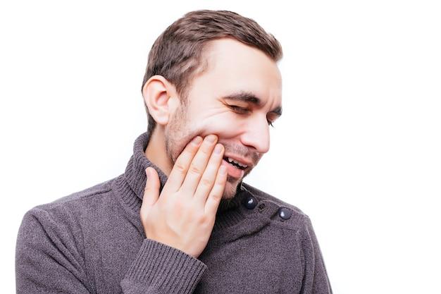 Knappe jonge man die lijdt aan kiespijn, zijn wang aanraakt om pijn tegen de witte muur te stoppen
