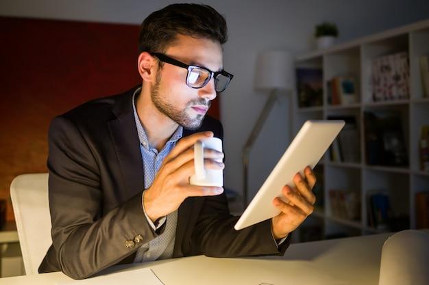 Knappe jonge man die met digitale tablet in het kantoor werkt.