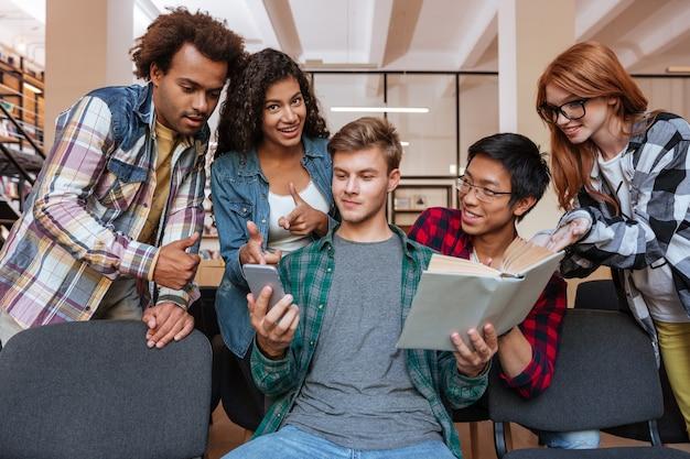 Knappe jonge man die mobiele telefoon leest en gebruikt terwijl zijn vrienden om hem heen staan