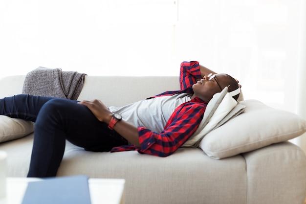 Knappe jonge man die naar muziek luistert met een koptelefoon thuis.