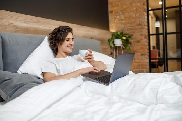 Knappe jonge man die 's ochtends op zijn bed ligt, een kopje koffie of thee vasthoudt en een laptop gebruikt