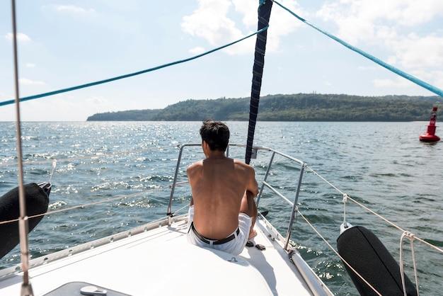 Knappe jonge man die van tijd op boot geniet