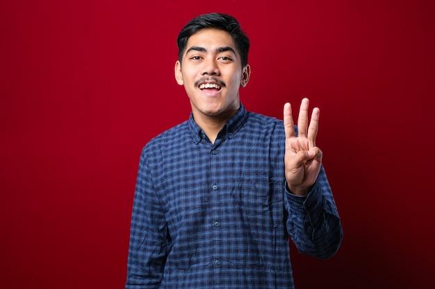 Knappe jonge man die vrijetijdskleding draagt en omhoog wijst met vingers nummer drie terwijl hij zelfverzekerd en gelukkig glimlacht over rode achtergrond