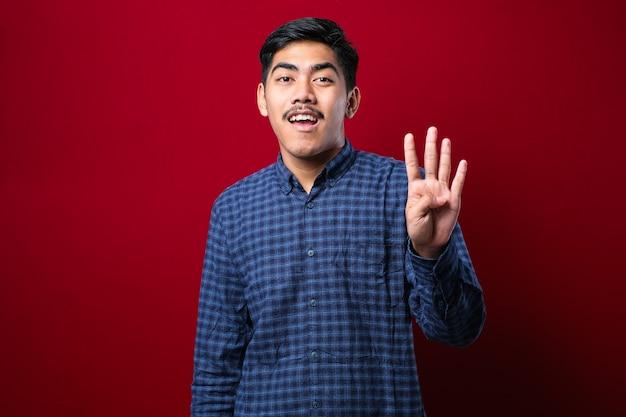 Knappe jonge man die vrijetijdskleding draagt en omhoog wijst met vingers nummer vier terwijl hij zelfverzekerd en gelukkig glimlacht over rode achtergrond