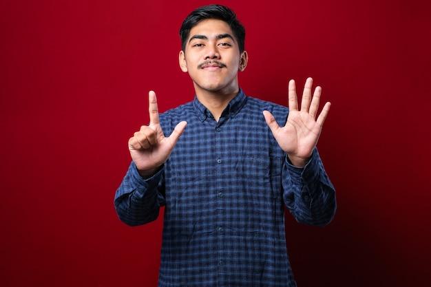 Knappe jonge man die vrijetijdskleding draagt en omhoog wijst met vingers nummer zeven terwijl hij zelfverzekerd en gelukkig glimlacht over rode achtergrond