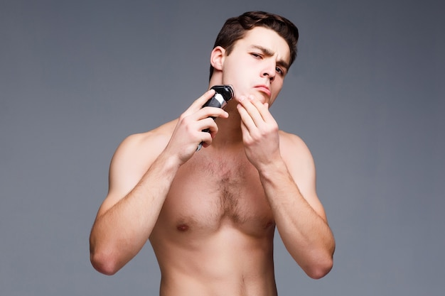 Knappe jonge man die zijn gezicht scheert met een elektrisch scheerapparaat en naar de voorkant kijkt