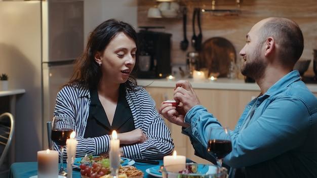 Knappe jonge man die zijn vriendin om huwelijk vraagt. man die zijn bruidsverloofde voorstelt om tijdens een romantisch diner in de keuken te zijn. blij verrast vrouw die lacht sprakeloos.