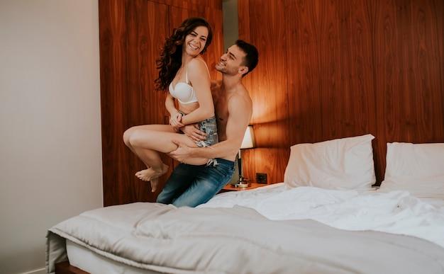 Knappe jonge man en mooie jonge vrouw met plezier in het bed