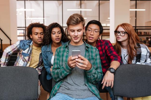 Knappe jonge man en zijn vrienden zitten en gebruiken samen mobiele telefoon