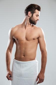 Knappe jonge man gekleed in handdoek