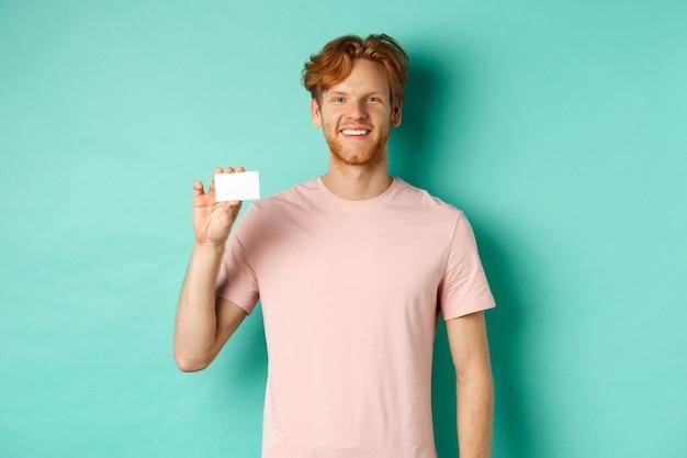 Knappe jonge man glimlachend en plastic creditcard tonen, permanent in t-shirt tegen turkooizen achtergrond.