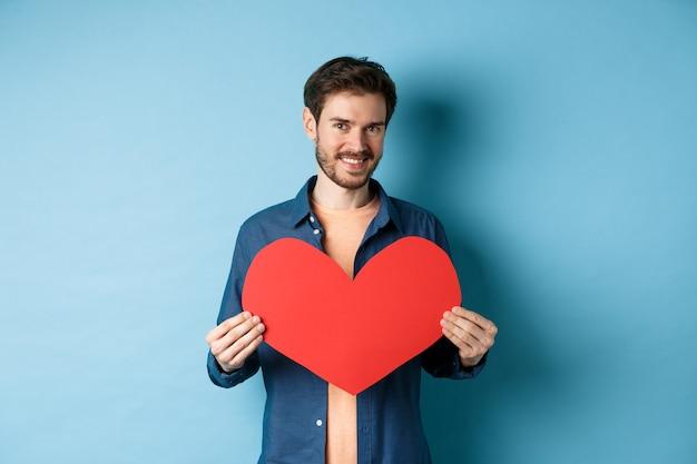 Knappe jonge man glimlachend, groot rood hart briefkaart tonen voor valentijnsdag, kijken camera gelukkig, staande tegen een blauwe achtergrond.