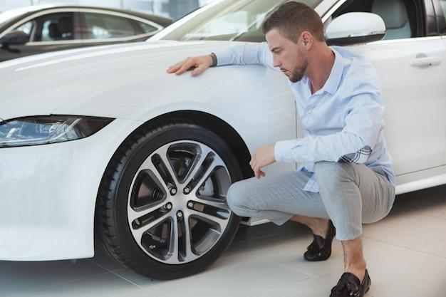 Knappe jonge man het kopen van een nieuwe auto op dealer salon