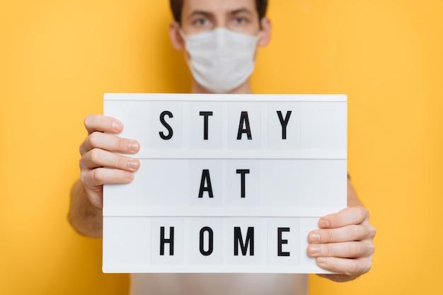 Knappe jonge man in beschermend masker houden thuis bordje vragen om zelfisolatie en sociale afstand nemen vanwege uitbraak van coronavirus