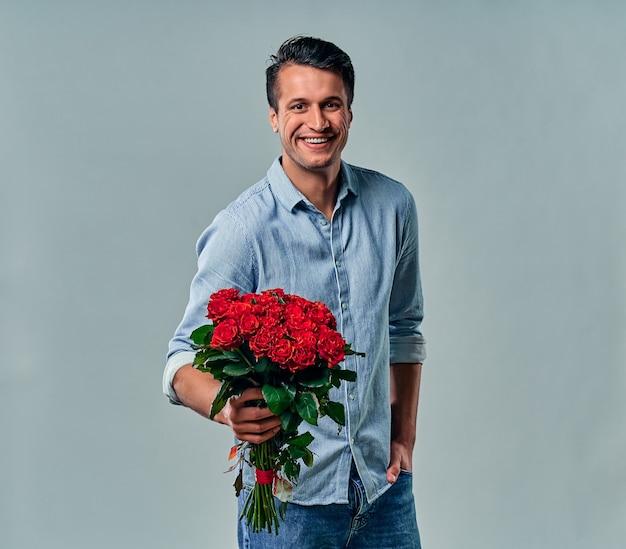 Knappe jonge man in blauw shirt staat met rode rozen op grijs