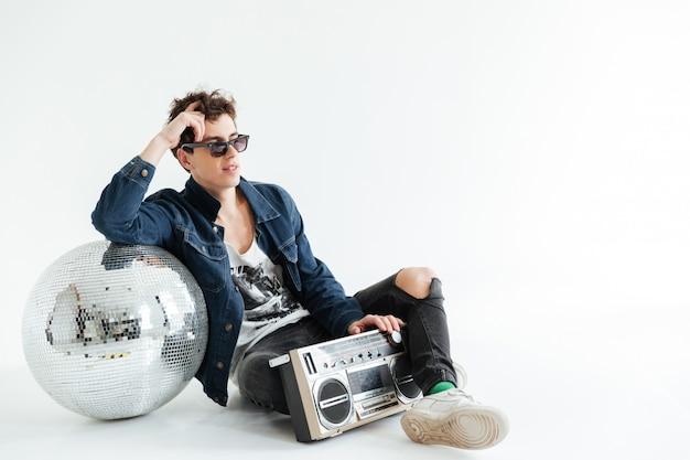 Knappe jonge man in de buurt van discobal en boombox