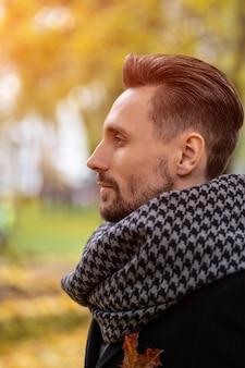Knappe jonge man in donkerblauwe jas en sjaal
