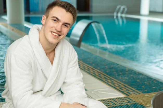 Knappe jonge man in een badstof badjas ontspannen bij het zwembad