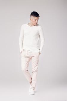 Knappe jonge man in een witte trui poseren