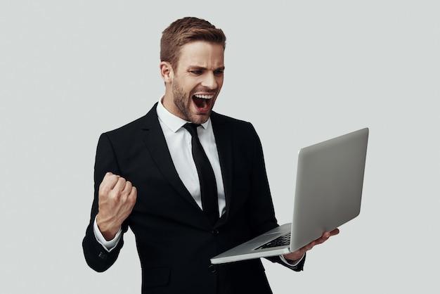 Knappe jonge man in formalwear die met laptop werkt en glimlacht terwijl hij tegen een grijze achtergrond staat