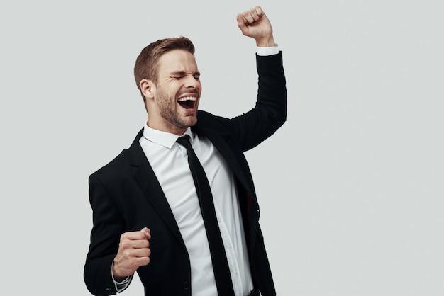 Knappe jonge man in formalwear juichen en gebaren terwijl hij tegen een grijze achtergrond staat