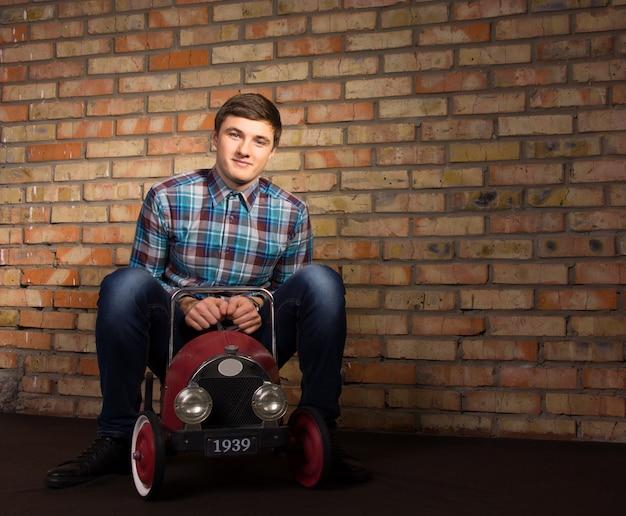 Knappe jonge man in geruit overhemd en jeans spelen met speelgoed auto met bakstenen muur achtergrond.