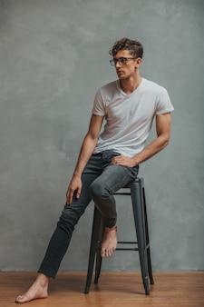 Knappe jonge man in glazen, gekleed in spijkerbroek en wit t-shirt poseren op blote voeten stoel.